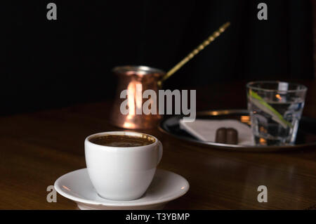 a glass of coffee with coffee pot and chocolate beside a coffee with milk in a white cup placed on a brown table - Stock Photo