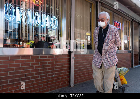 An elderly Asian man walking on Roosevelt Ave in Jackson Heights while wearing a face mask and being attached to an oxygen tank. In Queens, New York. - Stock Photo