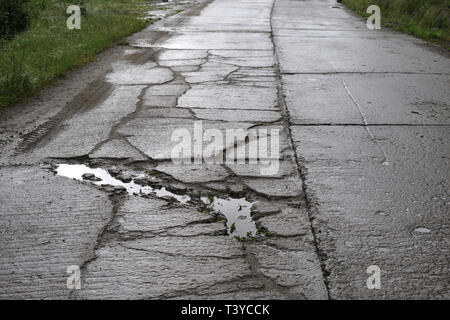 Damaged road in bad condition, Romania, Banat - Stock Photo