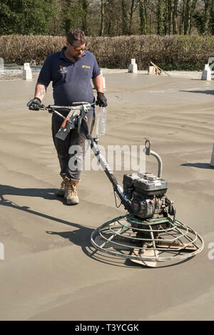 Presteigne, Powys, Wales, UK. A man using a power trowel (power float) to smooth the surface of a freshly laid concrete slab floor - Stock Photo