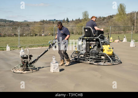 Presteigne, Powys, Wales, UK. Men using power trowels (power floats) to smooth the surface of a freshly laid concrete slab floor - Stock Photo