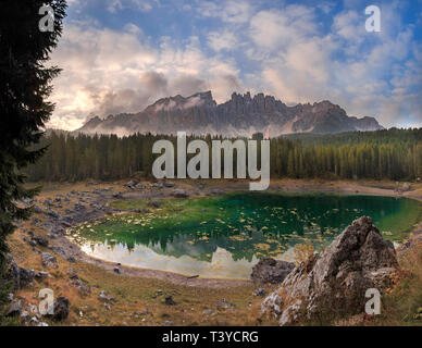 A gorgeous sunrise at the lake of Carezza, a wonderful lake surrounded by two of the most famous massifs  of the Italian Dolomites, the Catinaccio&Ros - Stock Photo