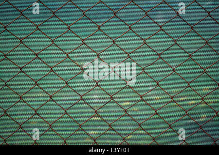 Rusty lattice fence. Old grid. Green striped fabric texture. Double opaque protection. Old metal wire mesh. Rough textile on background. Brown netting - Stock Photo
