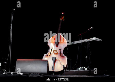 Cello (violoncello) in the center of an empty stage at a concert - Stock Photo