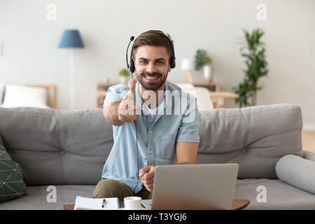 Head shot portrait happy smiling man in headset show thumbs up - Stock Photo