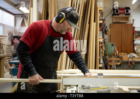 Carpenter using table saw in workshop - Stock Photo