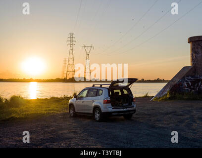 Car parked on rural lake shore - Stock Photo