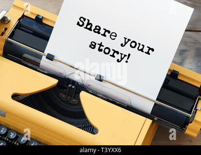 Share your story! Words written on yellow typewriter - Stock Photo