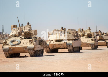 A group of Bradley Fighting Vehicles and M1 Abrams battle tanks assigned to 2nd Brigade Combat Team, 1st Armored Division, proceed in a line towards their destination during exercise Strike Focus, at Orogrande Range Camp, N.M., April 8, 2019.    Strike Focus is a multifaceted and multi-week long training exercise combining the numerous operational aspects of a brigade combat team in a cohesive operation emphasizing lethality, readiness and operability.    (U.S. Army photo by Spc. Matthew J. Marcellus) - Stock Photo