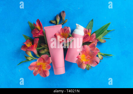Skin care cosmetics in pink palette in on a blue background with spring flowers. Natural cosmetics conceptual flat lay with copy space - Stock Photo