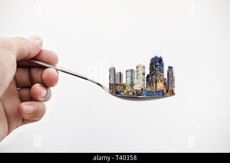 Real estate buildings on spoon, isolated on white background. Real estate and buildings concept - Stock Photo