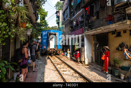 """""""Train street"""" in Hanoi, where twice a day a speeding train passes only centimetres away from the homes of this residential neighbourhood, Vietnam - Stock Photo"""