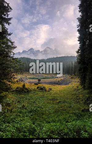 A view at sunrise of the woods surrounding the lake of Carezza (Karessee) and the peaks of the group of Catinaccio/Rosengarten in the background. Take - Stock Photo