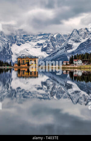 A tranquil view at sunrise of the Lake of Misurina, a lake in the Dolomiti d'Ampezzo, not far from the town of Cortina, with the majestic rocky walls  - Stock Photo