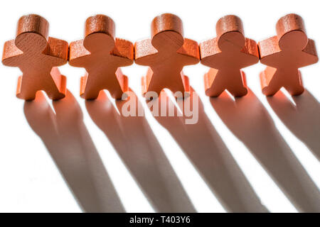 Wooden figures as a symbol of cohesion - Stock Photo