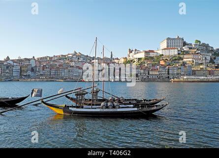 A view of a boat with wine barrels on the River Douro, Ribeira waterfront riverside & cityscape from Vila Nova de Gaia in Porto Portugal EU   KATHY - Stock Photo