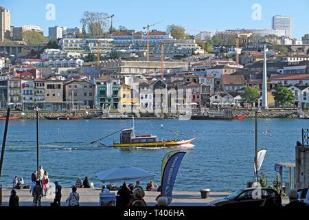 A view of a boat on the River Douro, Vila Nova de Gaia houses on riverside, people sitting on Ribeira waterfront quay Porto Portugal EU   KATHY DEWITT - Stock Photo