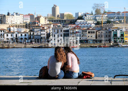 Two young women sitting together eating on the quay looking across the Douro River at Vila Nova de Gaia in Porto, Portugal Europe   KATHY DEWITT - Stock Photo