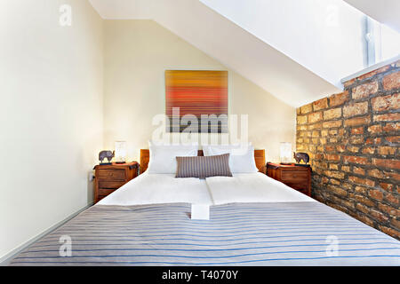 Bedroom interior in luxury loft, attic, apartment with roof windows - Hotel room - vacation concept background - Stock Photo
