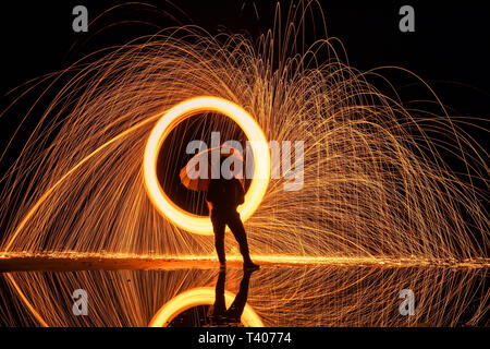 Light painting. Pyrotechnic display at night with the reflection of the water - Stock Photo
