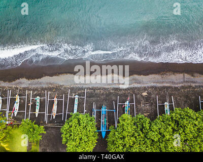 Top down aerial view of traditional Indonesian fishing boats called jukung on black sand beach. In Amed, Bali, Indonesia. - Stock Photo