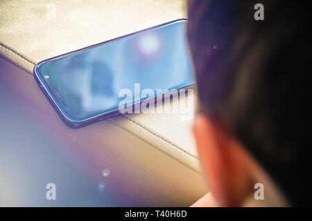 Little boy using a mobile phone at home - Stock Photo