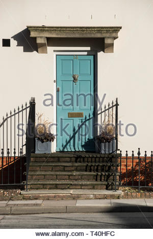 Sunny day image of a green front door with railings either side, Salisbury, Wiltshire, England, UK - Stock Photo