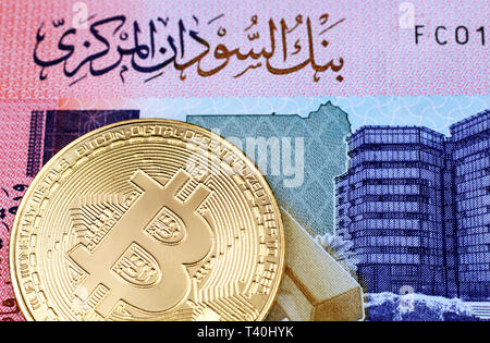 A close up image of a colorful Sudanese fifty pound bank note with a gold physical bitcoin in macro - Stock Photo