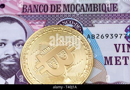 A macro image of a gold physical Bitcoin with a purple twenty metical note from Mozambique close up - Stock Photo