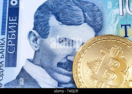 A close up image of a golden physical Bitcoin with a blue one hundred Serbian dinar bank note in macro - Stock Photo