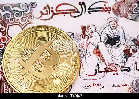 A macro image of a 200 Algerian dinar note with a gold, physical Bitcoin close up - Stock Photo