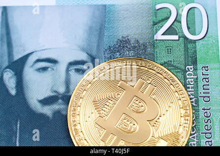 A close up image of a golden physical Bitcoin with a green twenty Serbian dinar bank note in macro - Stock Photo