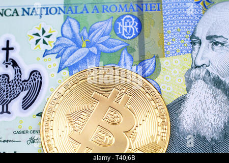 A close up image of a golden physical Bitcoin with a colorful Romanian one leu bank note in macro - Stock Photo