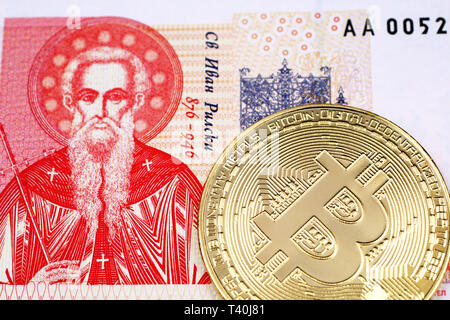 A close up image of a golden, physical Bitcoin with a Bulgarian one lev bank note in macro - Stock Photo