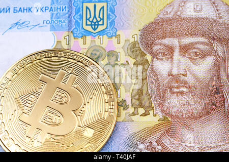 A close up image of a gold, physical Bitcoin with Ukranian one hryvnia bank note in macro - Stock Photo