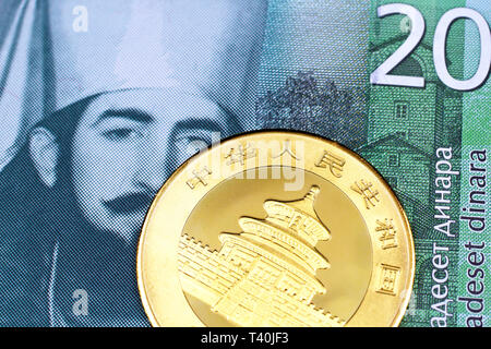 A close up image of a golden Chinese panda coin with a green twenty Serbian dinar bank note in macro - Stock Photo