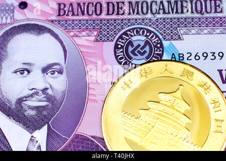 A macro image of a gold Chinese panda coin with a purple twenty metical note from Mozambique close up - Stock Photo