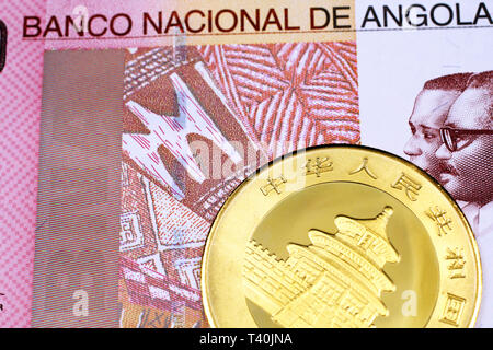 A macro image of a Chinese gold panda coin with a colorful one hundred Angolan kwanza bank note close up - Stock Photo