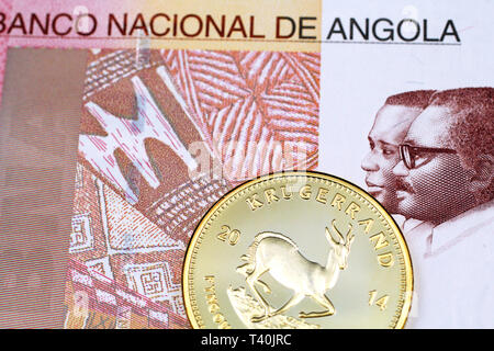 A macro image of a South African krugerrand gold coin with a colorful one hundred Angolan kwanza bank note close up - Stock Photo