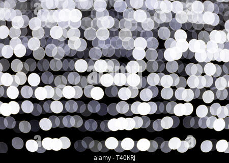 Abstract bokeh of white city lights on black background. defocused and blurred many round light. - Stock Photo