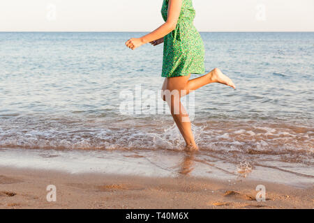 Leg of woman running on beach with water splashing. summer vacation. legs of a girl walking in water on sunset. - Stock Photo