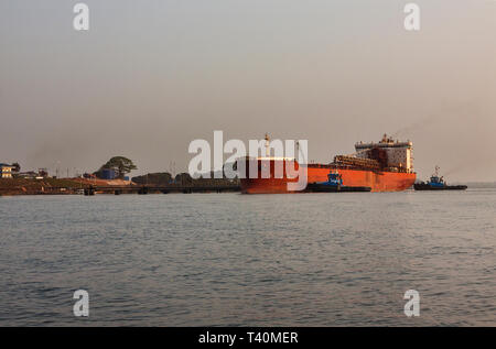 Port operations for managing and transporting iron ore. Tugs pushing and moving transhipper vessel to dock at layby jetty before move to loading jetty - Stock Photo