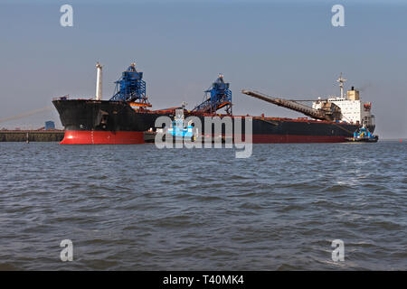 Port operations for managing and transporting iron ore. Transhipping boat and tugs prepare to set sail to unload into OGV - Ocean Going Vessel at sea - Stock Photo