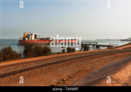 Port operations for managing and transporting iron ore. Across ore train rail loop to TSV ship moored at layby jetty before moving to loading jetty. - Stock Photo