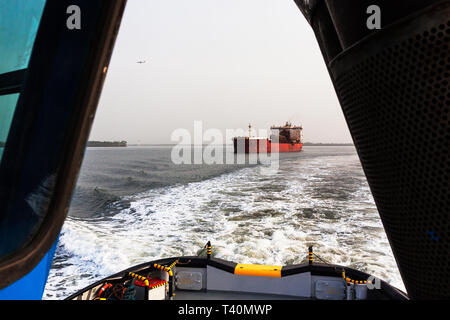 Port operations managing and transporting iron ore. From leading tug to transhipper or TSV in shipping channel to meet OGV ocean going ship  at sea - Stock Photo