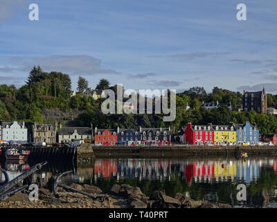 View at the harbour and the colourful houses of Tobermory with their reflections on the water surface on the Isle of Mull in Scotland - Stock Photo
