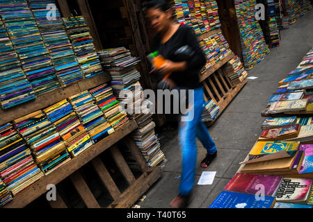 A Salvadoran woman walks along hundreds of used books stacked in shelves on the street in a secondhand bookshop in San Salvador, El Salvador. - Stock Photo