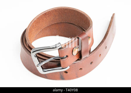 A product shot of a men's brown belt with patina set on a plain white background. - Stock Photo