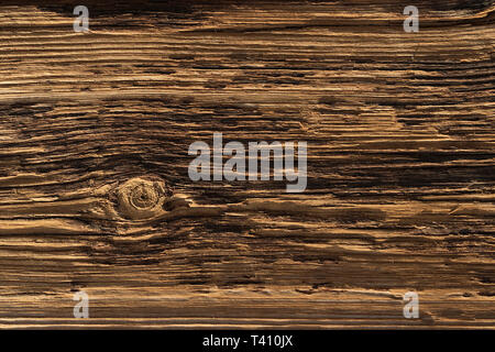 a deeply textured weathered old wooden board with with a single knot breaking the pattern - Stock Photo