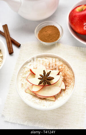 Oatmeal porridge with red apple slices and cinnamon. Healthy diet breakfast concept. Top view - Stock Photo